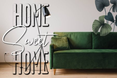 Photo for Green sofa with pillow near modern floor lamp, drawn plants illustration and home sweet home lettering - Royalty Free Image
