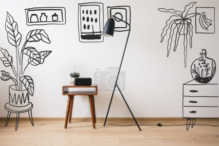 Photo for Floor lamp, wooden coffee table and clock with blank screen near drawn plants, paintings and dresser - Royalty Free Image