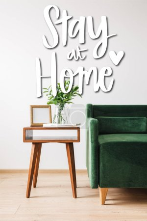 Photo for Green sofa near coffee table with plant, books, photo frame and stay at home lettering - Royalty Free Image