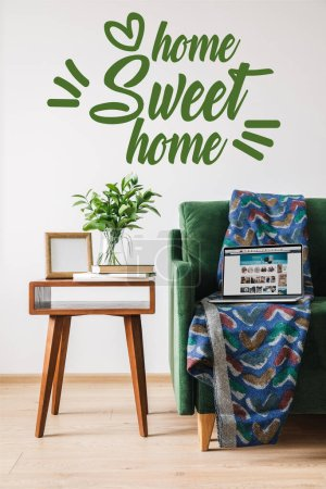 Photo for KYIV, UKRAINE - APRIL 14, 2020: home sweet home lettering near green sofa, blanket, laptop with amazon website and wooden coffee table - Royalty Free Image