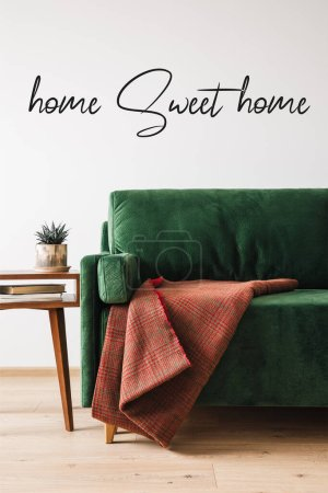 Photo for Green sofa, blanket and wooden coffee table with plant and books near home sweet home lettering - Royalty Free Image