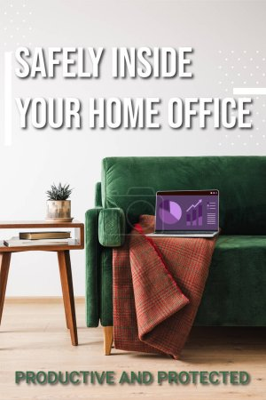 Photo for Green sofa, blanket and laptop with charts and graphs near safely inside your home office lettering, wooden coffee table with plant and books - Royalty Free Image