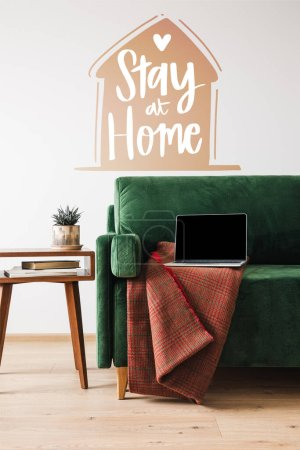 Photo for Green sofa with blanket and laptop near wooden coffee table and stay at home lettering - Royalty Free Image