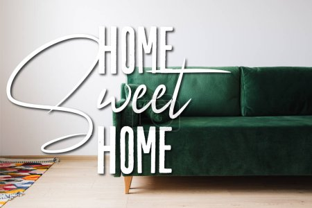 Photo for Green sofa with pillow near colorful rug and home sweet home lettering - Royalty Free Image