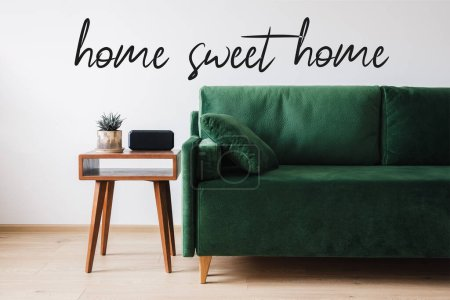Photo pour Canapé vert, oreiller, table basse en bois avec plante et réveil près de la maison lettrage doux maison - image libre de droit