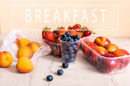 Photo for Blueberries, strawberries, nectarines and peaches in plastic containers on wooden surface near breakfast lettering on beige - Royalty Free Image