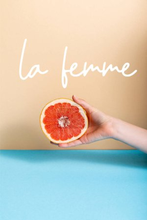 Photo for Cropped view of female hand with juicy grapefruit half near la femme lettering on beige and blue - Royalty Free Image