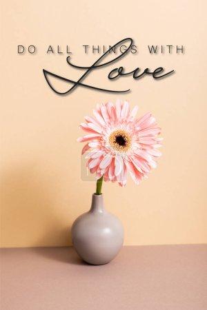 Photo pour Gerbera rose dans le vase près de faire toutes choses avec l'amour lettrage sur beige - image libre de droit
