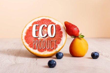 Photo pour Composition de fruits avec des baies, pamplemousse et abricot près de lettrage éco-produit sur beige - image libre de droit