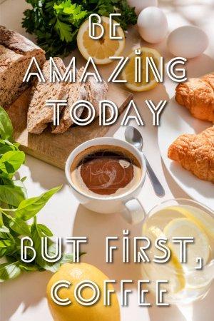 Photo pour Croissants frais, pain, verdure, oeufs, eau de citron et tasse de café pour le petit déjeuner sur la table grise avec être incroyable aujourd'hui, mais d'abord, lettrage café - image libre de droit