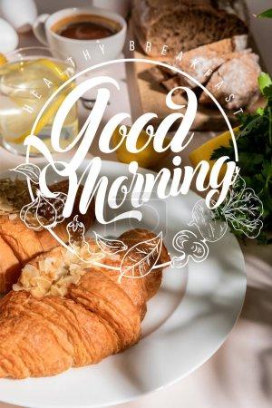 Photo pour Croissants frais, pain, café et eau de citron sur table grise, mise au point sélective avec petit déjeuner sain, lettrage bonjour - image libre de droit