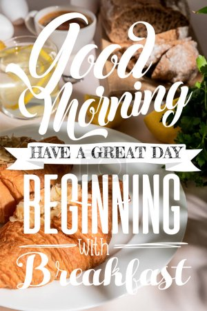 Photo for Fresh croissants, bread, coffee and lemon water on grey table, selective focus with good morning, have a great day, beginning with breakfast lettering - Royalty Free Image