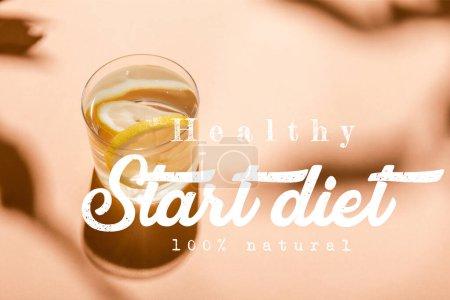 Photo pour Verre d'eau douce avec tranches de citron sur beige avec régime alimentaire sain 100 pour cent lettrage naturel - image libre de droit