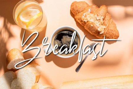 Photo pour Vue de dessus du café, de l'eau, de la baguette et du croissant sur table beige avec lettrage petit déjeuner - image libre de droit