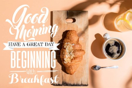 Photo for Top view of coffee, water and croissant on wooden board on beige table with good morning, have a great day, beginning with breakfast lettering - Royalty Free Image