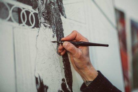 Photo pour Main masculine de l'artiste dessine avec stylo à encre, image monochrome du chien, vue de côté, gros plan - image libre de droit