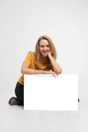 Photo for Young woman with blond hair, wearing casual outfit, boots, is sitting on white floor, holding white makeup poster, isolated on white background - Royalty Free Image