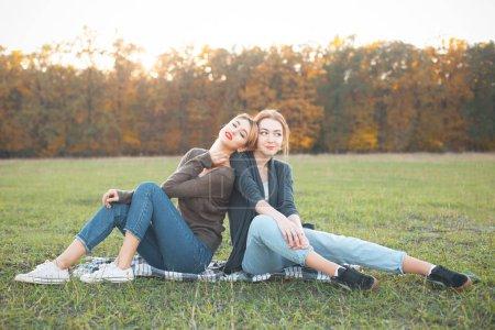 Foto de Dos niñas sentadas en el césped. Mejores amigos - Imagen libre de derechos