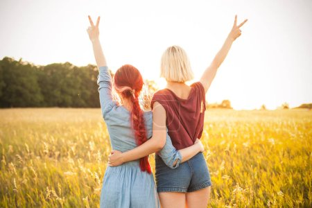 Photo for Two beautiful young women spend time together outdoors. Best friends - Royalty Free Image