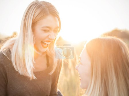 Photo for Two cheerful young female having fun outdoors at sunset - Royalty Free Image