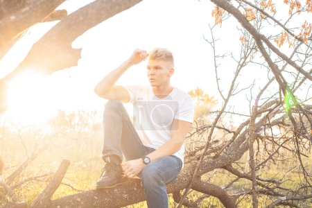 Photo for Young man with white shirt posing near the tree - Royalty Free Image