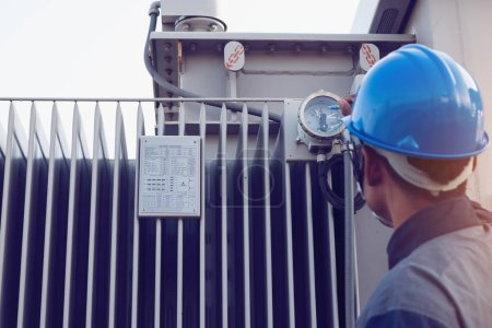 Photo for Engineer or electrician working on checking and maintenance equipment at green energy solar power plant; checking status step up transformer high voltage at transformer yar - Royalty Free Image