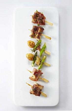 Photo pour Gros plan d'une plaque blanche avec collations de viande et légumes frites sur des petites brochettes en bois - image libre de droit