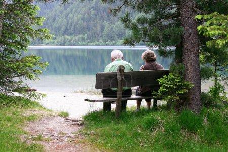 Photo pour Un couple âgé assis sur un banc au bord du lac - image libre de droit