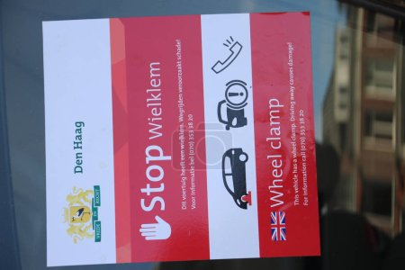 Photo pour Autocollant sur la voiture pour avertir que la municipalité a mis un collier de serrage sur elle et sera retiré lorsque l'amende de stationnement est payée à La Haye, Pays-Bas - image libre de droit