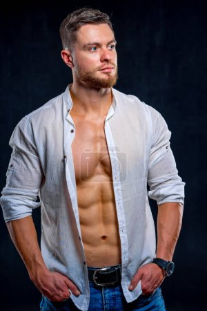 Photo for Super sexy man with tan abs and chest. Athletic man with unbuttoned white shirt on dark background. Studio portrait - Royalty Free Image