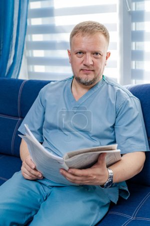 Photo for Portrait of a doctor or medical specialist. Vertical portrait. Man in scrubs. Papers in hands. - Royalty Free Image