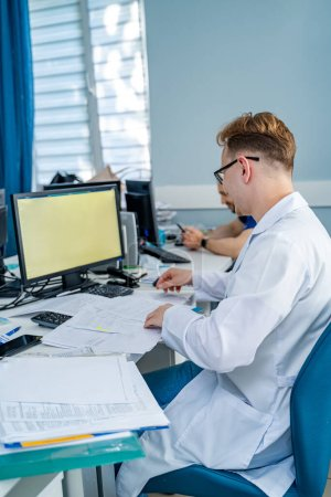 Photo for Man sitting at desk. Doctor in scrubs at office near computer. Office in hospital. - Royalty Free Image