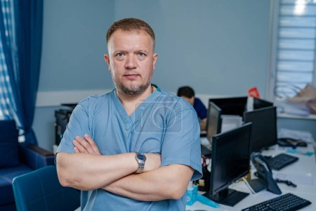 Photo for Doctor stands cross hands. Blue scrubs. Office in hospital background. - Royalty Free Image