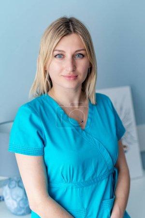 Photo pour Portrait de jeune infirmière chirurgicale en blouse regardant vers la caméra. Portrait de femme médecin dans une clinique moderne. - image libre de droit