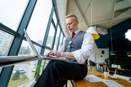 Photo for Thoughtful middle aged businessman in suit. Sitting with a laptop near the window. Man working with documents. Business concept. - Royalty Free Image