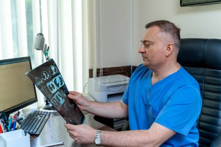 Photo for Doctor in scrubs sitting at office. X-ray in hands. Medical results at doctor s hands. - Royalty Free Image