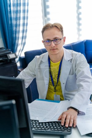 Photo for Serious doctor sitting at computer. Medical office. Doctor at work. Diagnosing. - Royalty Free Image