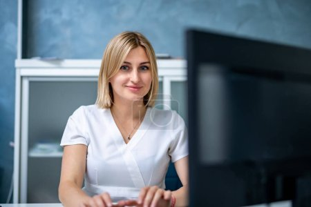 Photo for Young female doctor typing on laptop computer while sitting at the table in hospital office. - Royalty Free Image