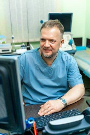 Photo pour Médecin joyeux près de l'ordinateur. Équipement d'échographie sur le fond. - image libre de droit