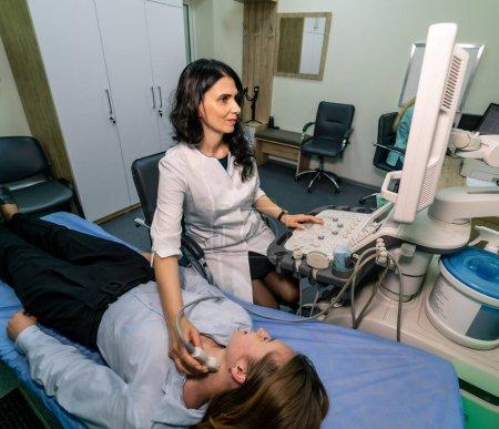 Photo pour Une femme se fait échographier au cabinet médical. Machine à ultrasons, échographie. Vue d'en haut. - image libre de droit
