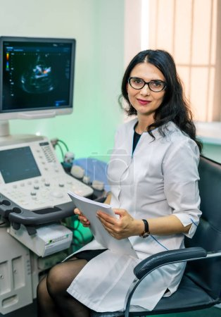 Photo for Professional sonographer sitting near modern ultrasound machine in clinic. - Royalty Free Image