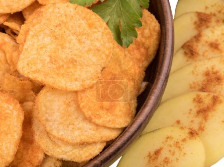 Closeup of crispy potato chips with salt and pepper as a background. Junk food and fast snack concept.