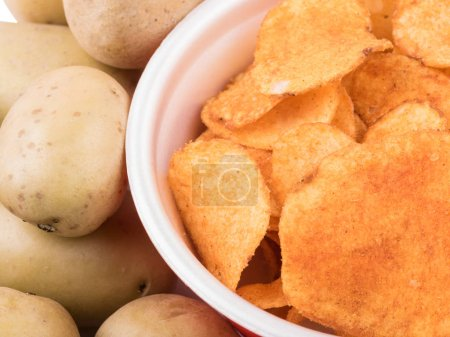 Photo for Closeup of crispy potato chips with salt and pepper as a background. Junk food and fast snack concept. - Royalty Free Image