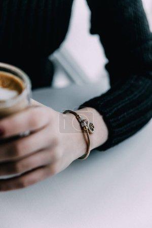 A close-up of a gold bracelet on the wrist of a gi...