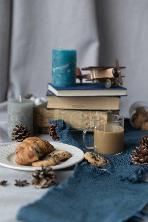 Photo pour Une tasse de verre transparente se tient sur une table avec une nappe bleue, il y a du café, il y a des biscuits dans une assiette, il y a des livres les uns sur les autres sur les livres il y a une bougie, - image libre de droit