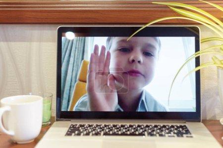 Photo pour Écran flou de webcam d'ordinateur portable du garçon ayant le chat vidéo pendant la quarantaine en raison de la pandémie de coronavirus - image libre de droit