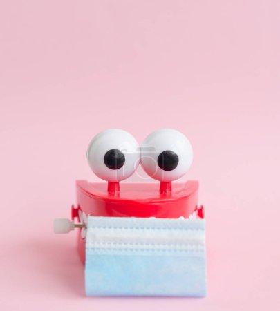 Photo pour Jouet avec des dents et des yeux souriants avec masque facial sur fond rose comme concept de dentisterie et de cavité buccale saine et sourire pendant la pandémie - image libre de droit