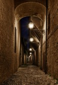 Forli, Emilia Romagna, Italy: narrow dark alley in the old town - ancient Italian street at night with lampposts and cobbled pavement