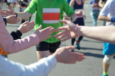 Marathon running race, supporting runners on road, child's hand giving highfive, sport concept