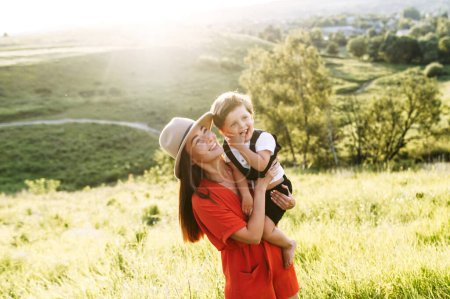 Photo for Young beautiful mother holds her four years alo son. They are standing in the middle of a green field and laughing wearing smart casual clothes - Royalty Free Image